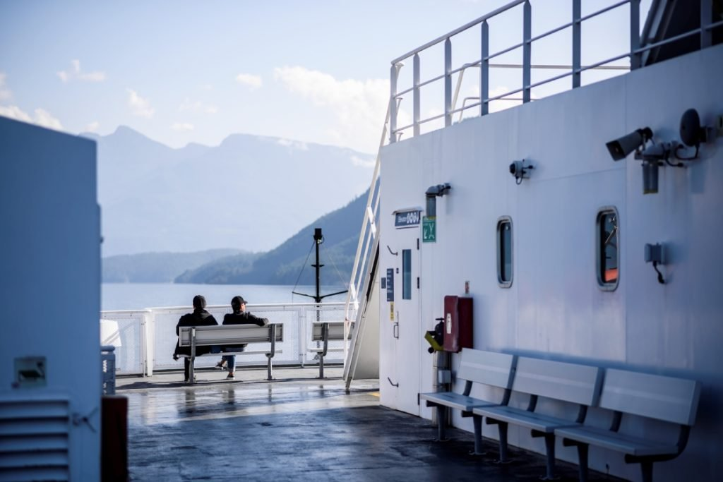 A couple sits on the deck of a ferry, taking in the view of the mountains.