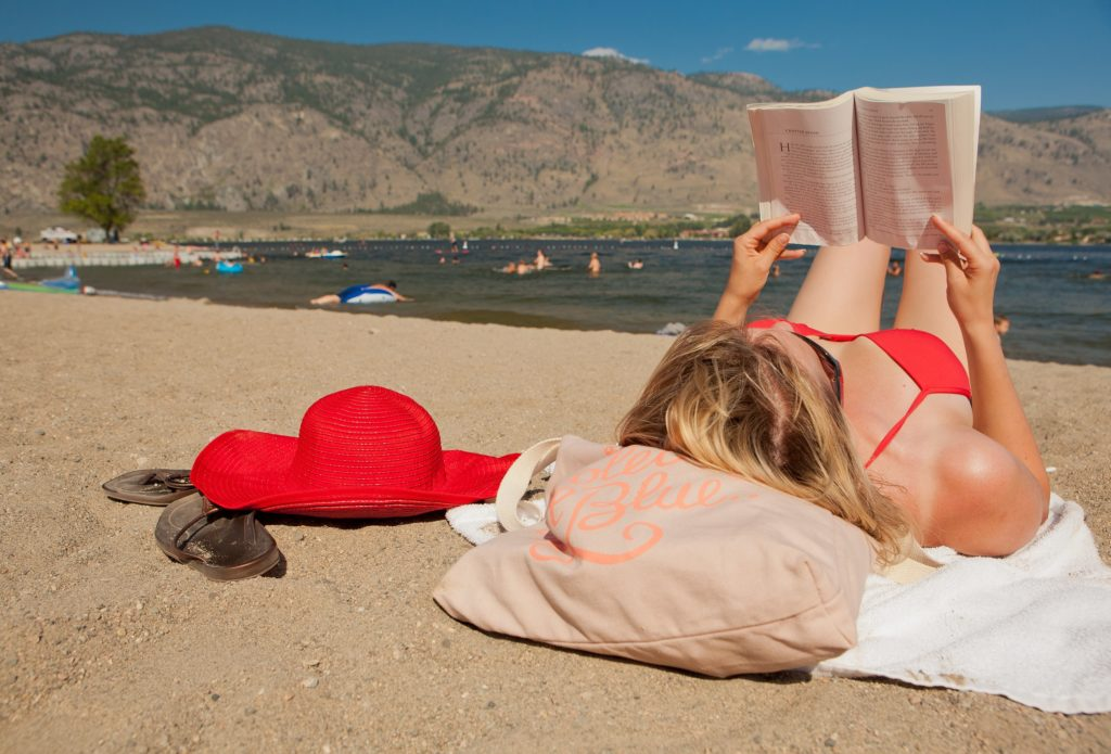 A woman in a red bathing suit reads a book on the beach.