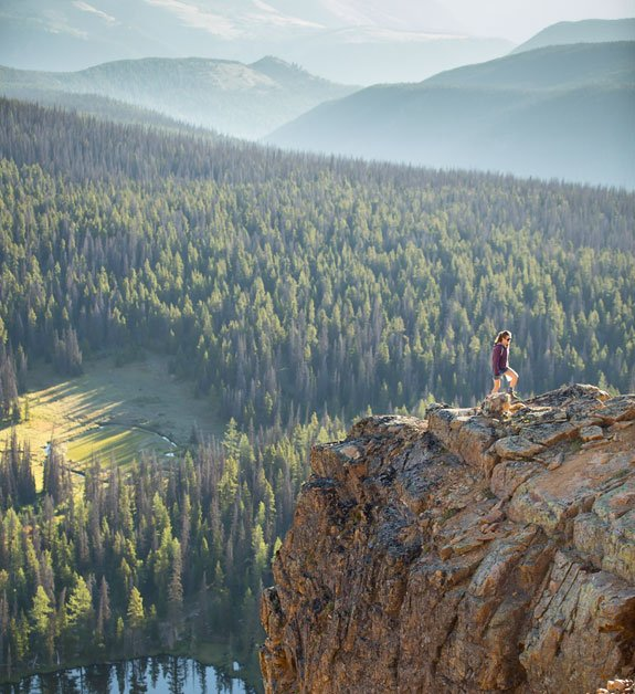 A woman hikes a tall rock formation that looks out over a dense forest.