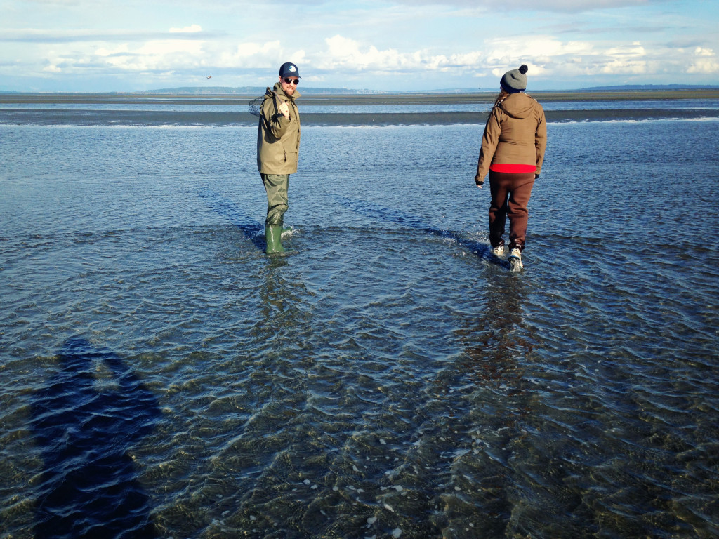 Two crab fishermen heading out in hip waders at low tide.