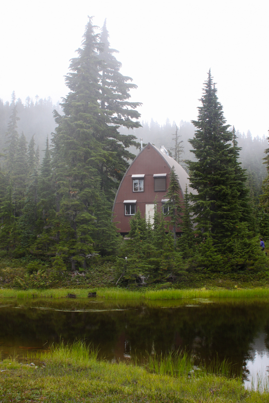 A brown a-frame cabin looks out over a body of water on a foggy day.