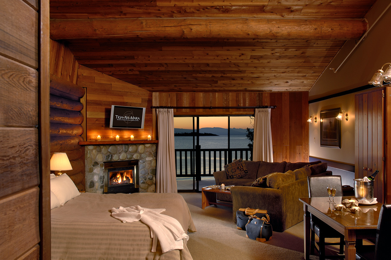 A luxurious hotel room with a fireplace and private balcony balcony overlooking the water at sunset.