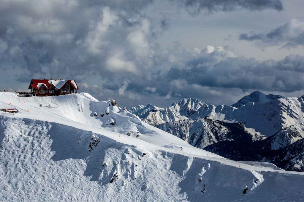 View of the lodge at peak of Kicking Horse Mountain Resort and surrounding mountains.