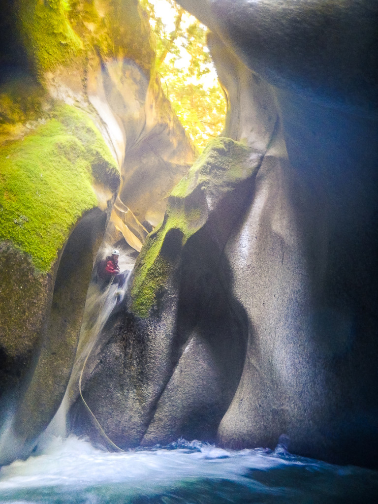 A woman rappels down a waterfall inside a canyon.
