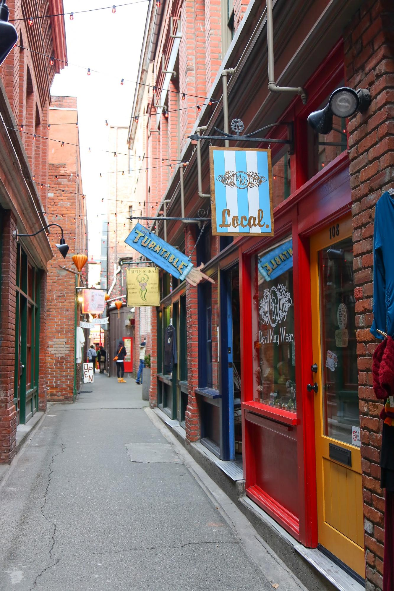 A narrow alleyway lined with colourful shops.