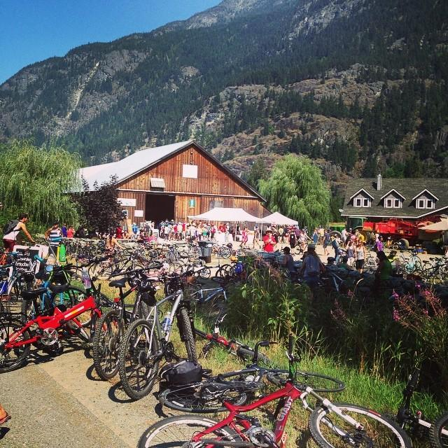 The side of the road is full of bikes, leading into a busy outdoor market.