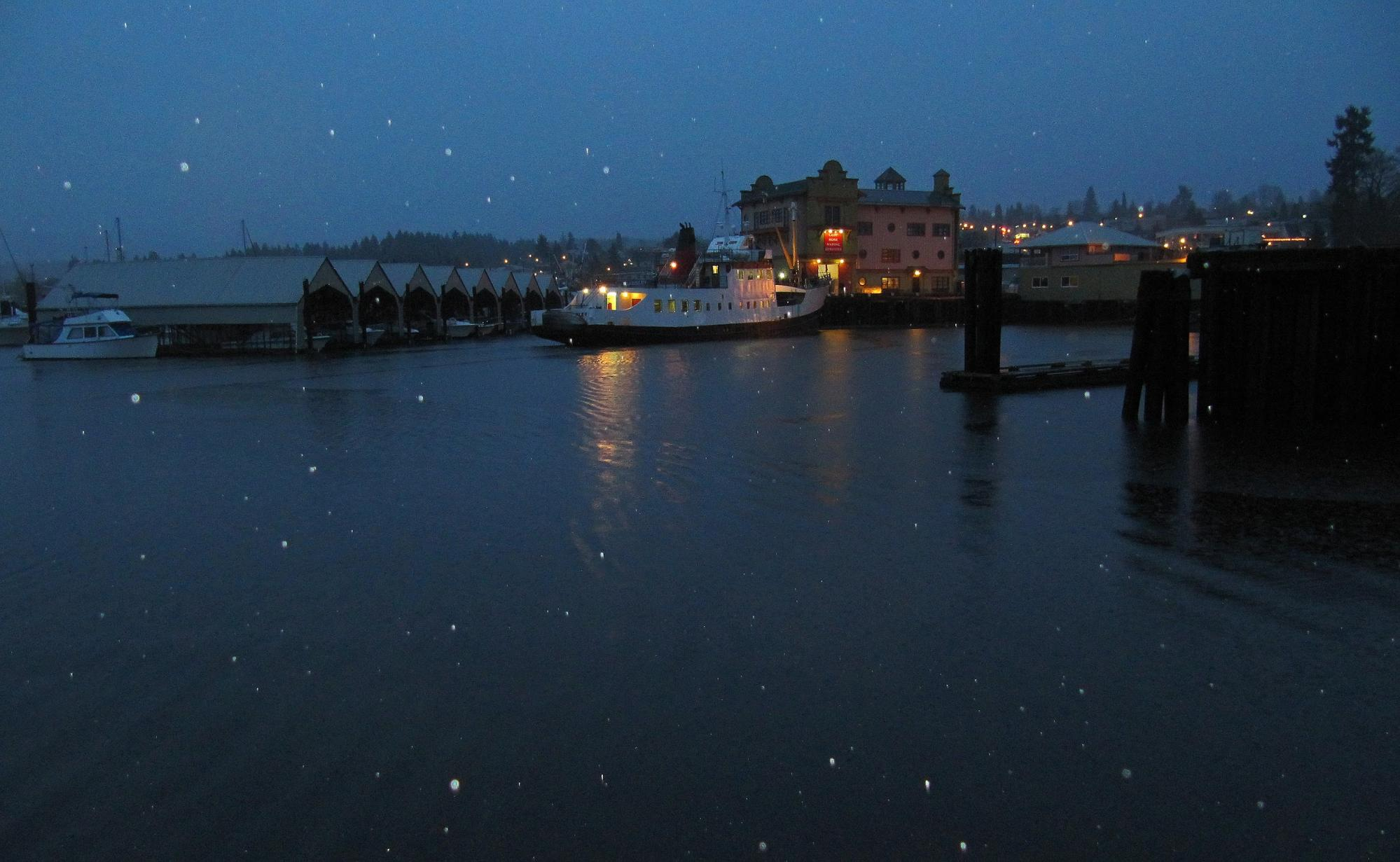 Snow softly falls over a quiet harbour at night.