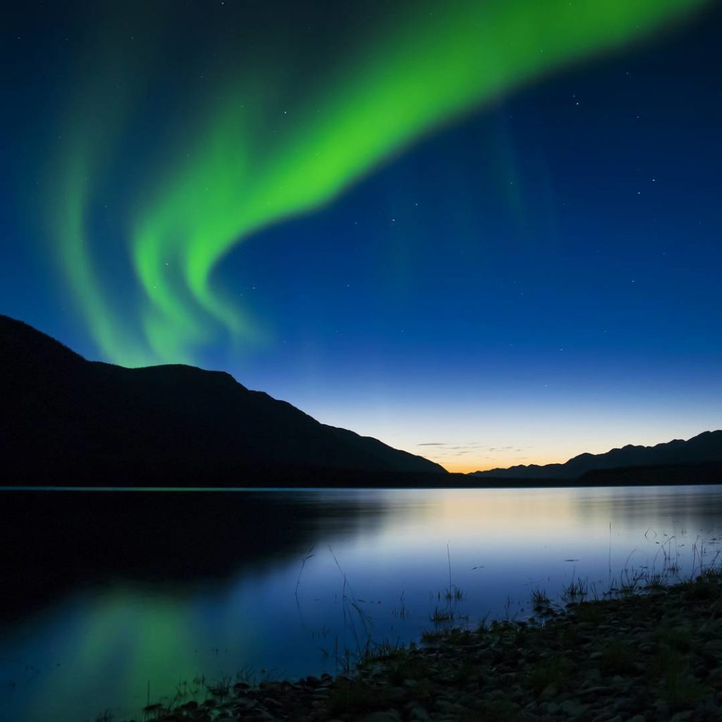 The Northern Lights shine neon green over a tranquil lake.