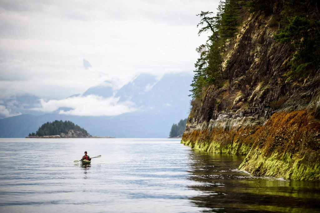 A kayaker paddles along a rocky coastline.