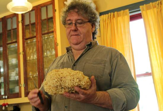 A man holds a large piece of cauliflower fungus.