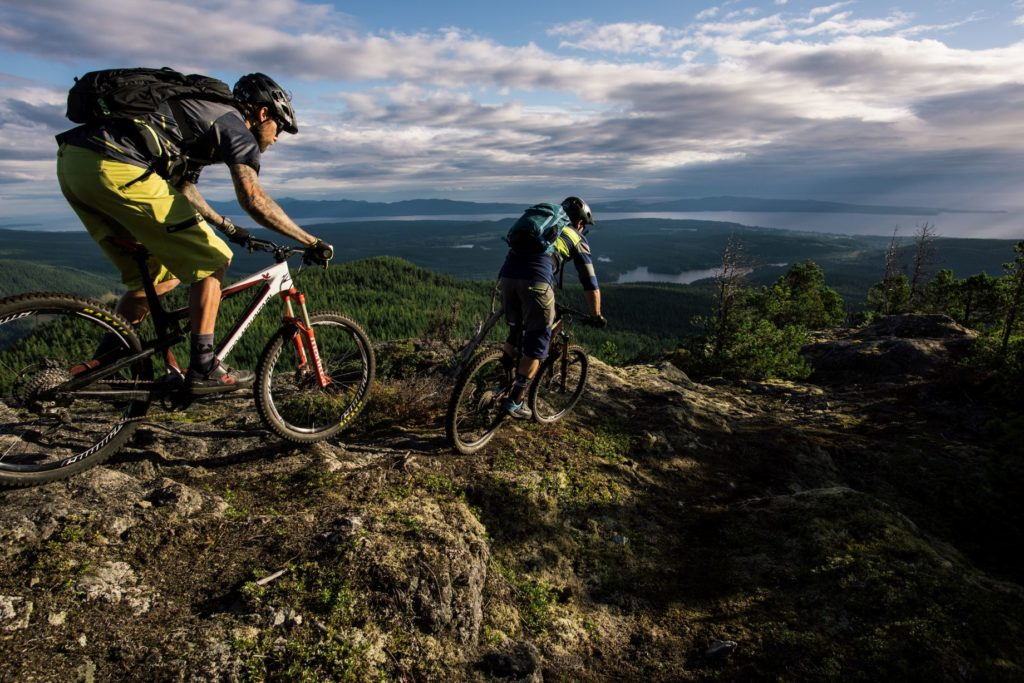Two mountain bikers travel across a rocky landscape.