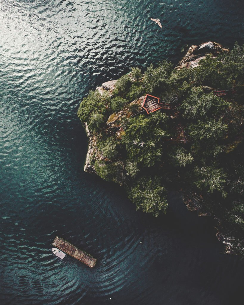 Aerial view of a lush island and a floating dock just offshore.