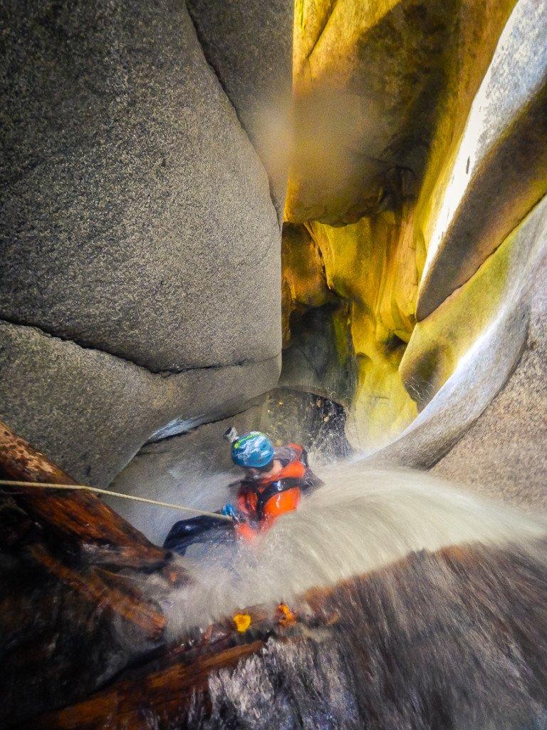 A woman rappels down beautiful granite walls, sculpted by water.