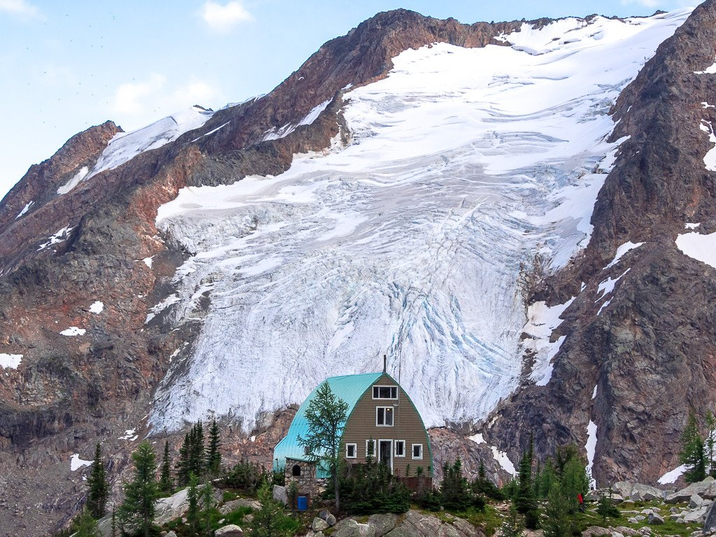 A brown cabin with a blue roof stands in front of a massive glacier.