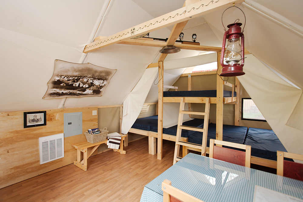 The interior of an oTENTik tent with bunk beds and light touches of wood.