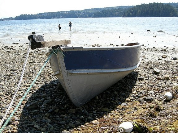 A small boat is pulled up onto a rocky beach.
