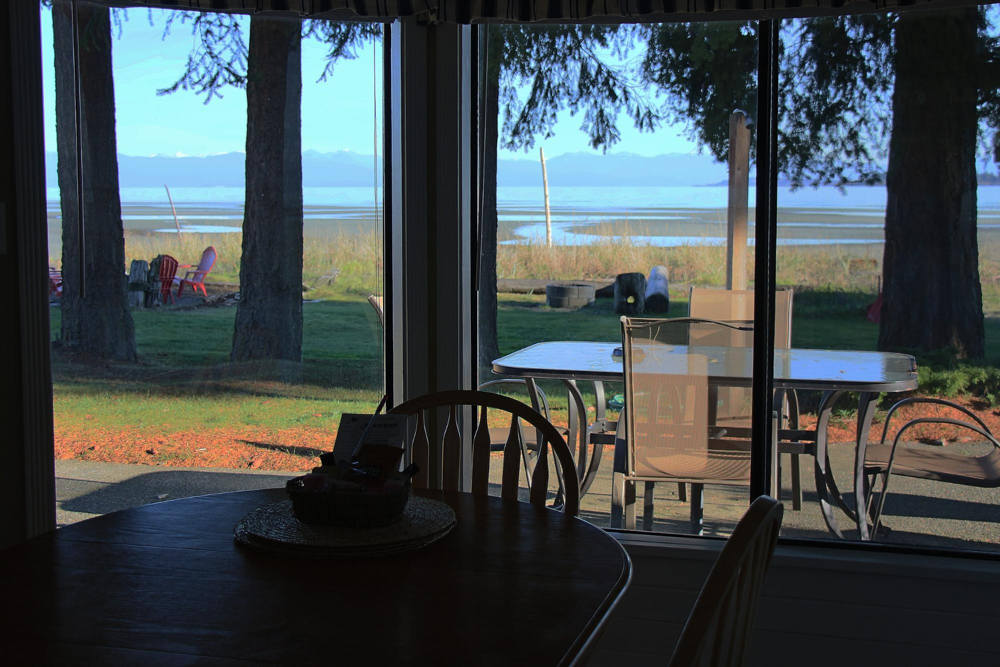 The view from the window of a beach-front accommodation looks out over the water.