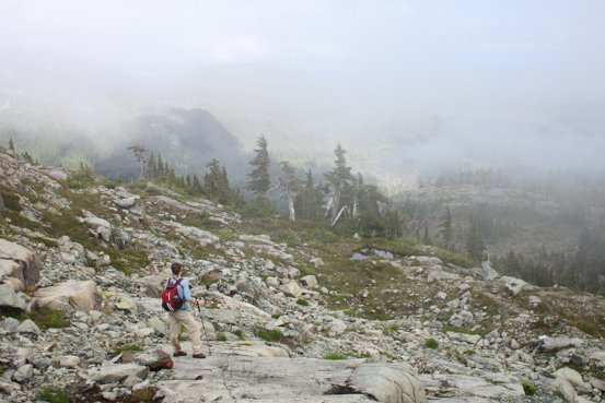 A hiker travels over a rocky terrain on a foggy day.