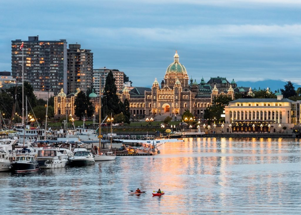 Two kayakers paddle through Victoria's inner harbour at sunset.