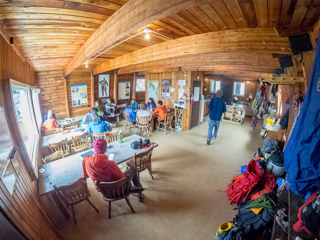 The interior of the Conrad Kain Hut, filled with backpackers dining at tables.