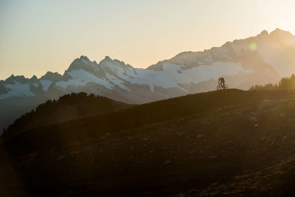 Silhouette of a mountain biker cycling in front of a range of snow-capped mountains.