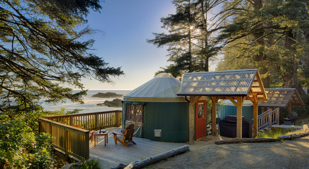 An eco-yurt looks out over the ocean at sunset.