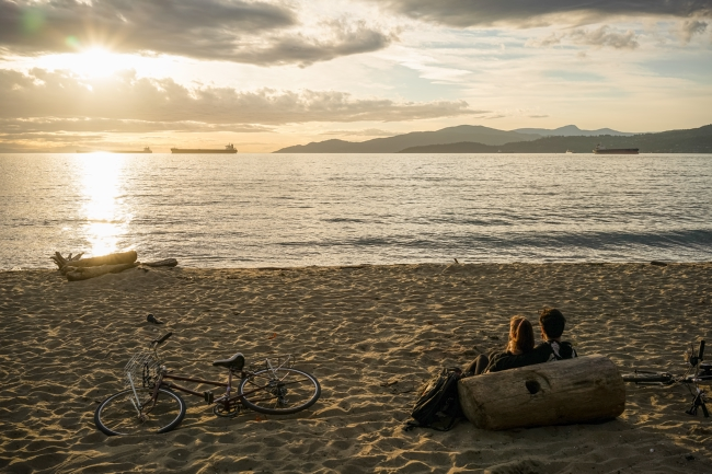 A couple enjoying the sunset at Vancouver's Third Beach with their bikes in the sand. Photo: Maurice Li