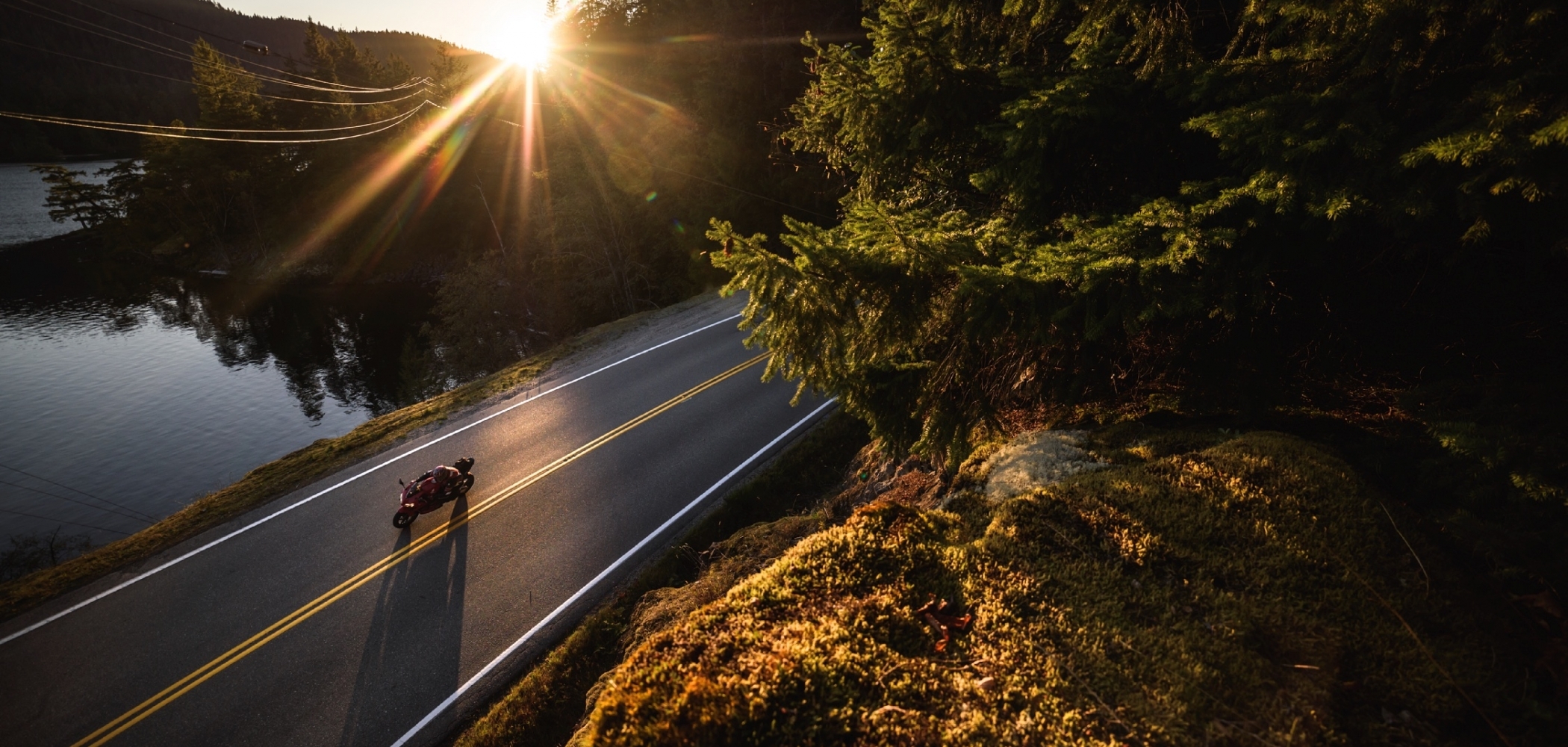 A motorcycle out for a sunset ride past Ruby Lake on the Sunshine Coast Highway, BC
