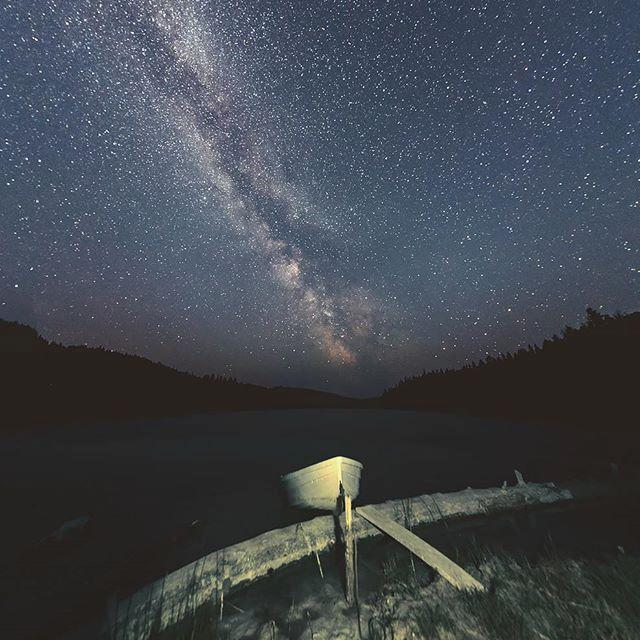 A star-filled sky over a small boat anchored close to shore.