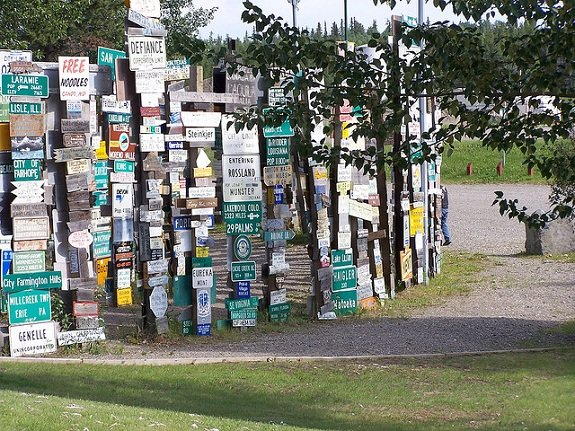 Posts filled with hundreds of town signs line a trail on a sunny day.