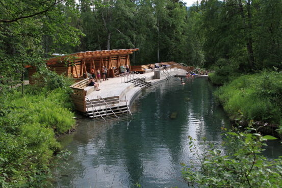 A sprawling wharf on the edge of a hot spring, surrounded by lush vegetation.