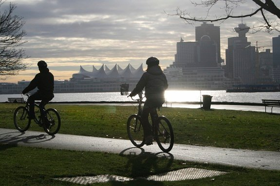 Two cyclists cycling along the Stanley Park Seawll in Vancouver on a cloudy day with the city skyline in the background.