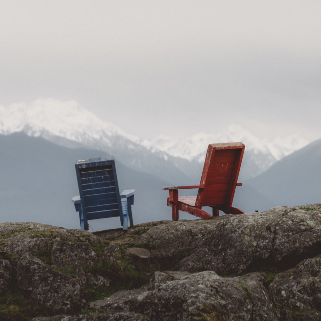 One red and one blue outdoor chair sit on a rock, looking out at a snow-covered mountain.