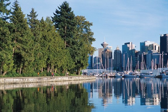 Stanley Park's seawall on the left with the ocean in the centre with Vancouver's skyline reflecting in it.