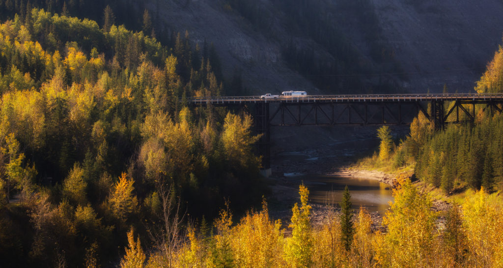 Vehicles travel across a bridge in a landscape dotted with bright fall foliage.