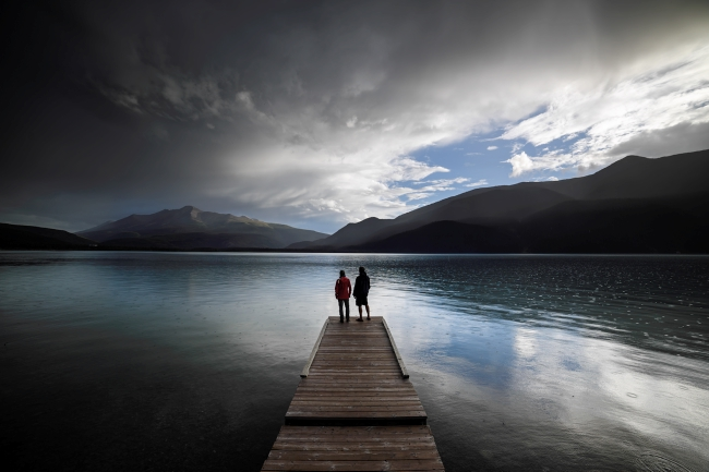 Two people stand at the edge of a dock, taking in the mountain views as evening creeps in.