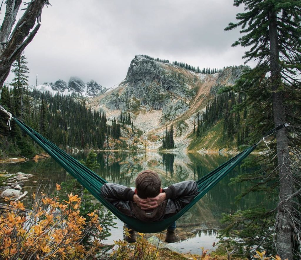 A man relaxes in a hammock overlooking a small pond and a rocky mountain.