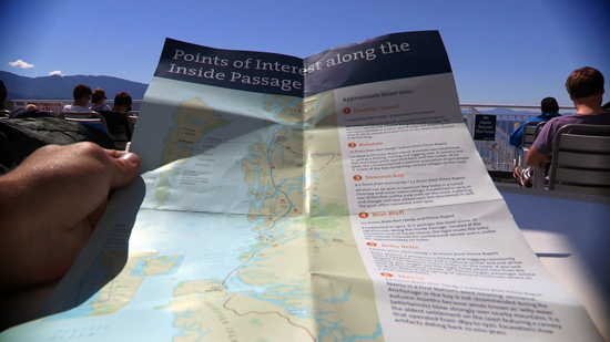 "Hands hold open a map titled ""Points of Interest Along The Inside Passage""."