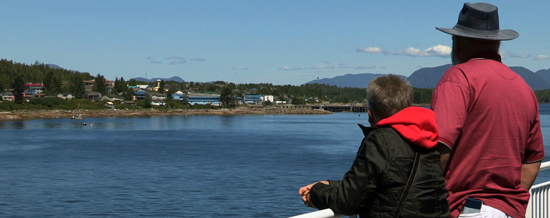 An older man and a young boy take in the view of the coast from the deck of a ferry.