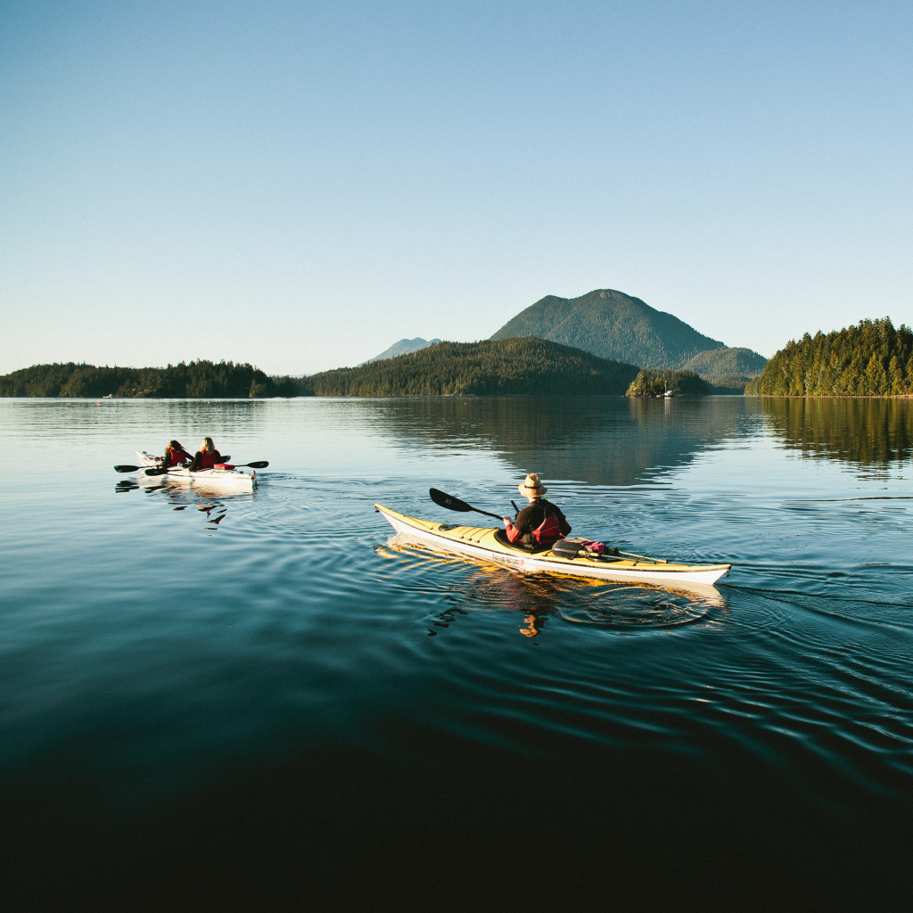 Two kayakers enjoying a sunset paddle with Tofino Sea Kayaking in the Tofino Harbour by @jeremykoreski