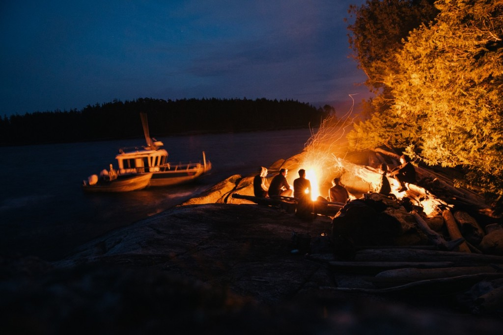 Sitting around the campfire at Nimmo Bay Resort. Photo: @jeremykoreski