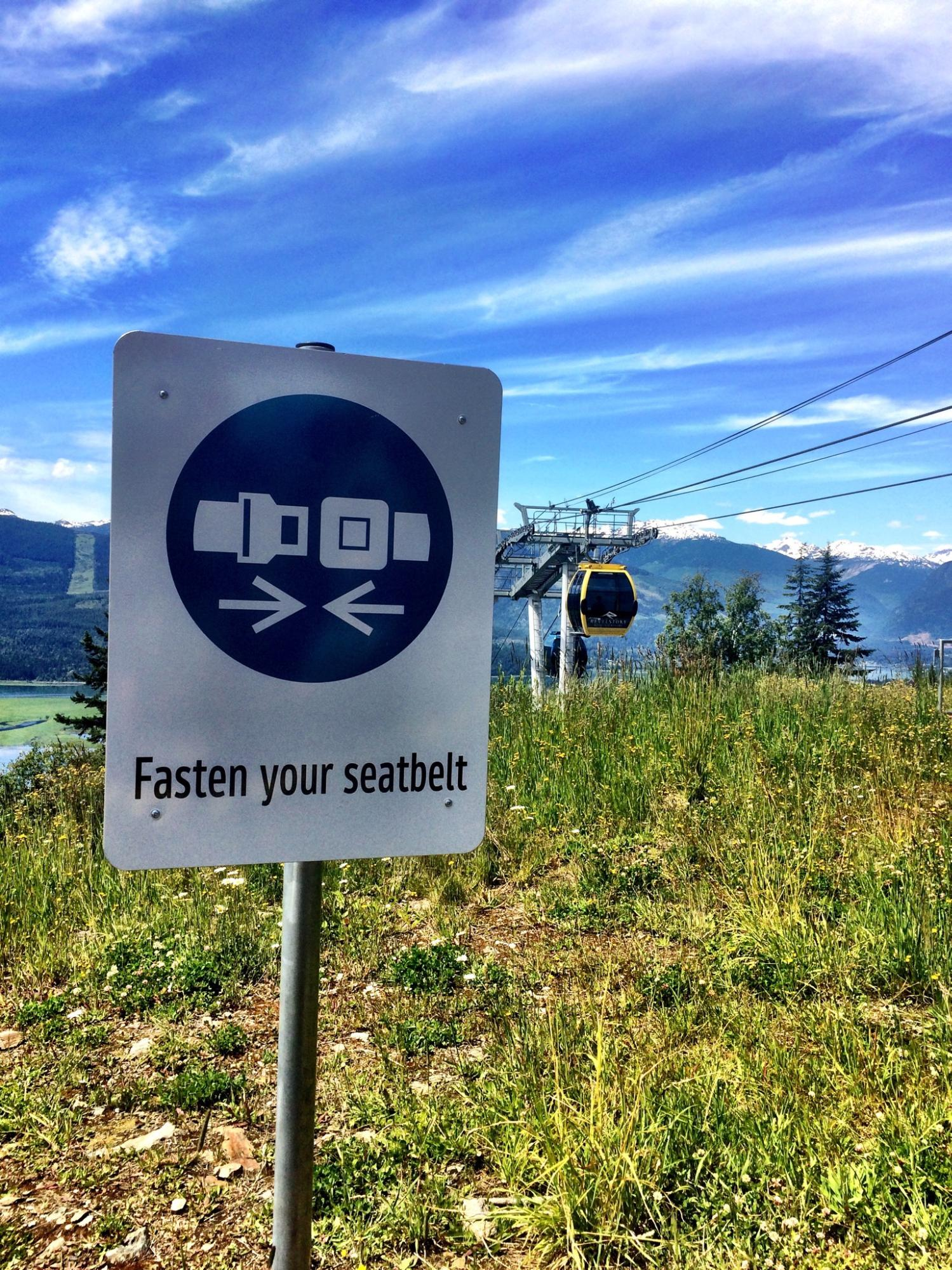 "A sign that reads ""fasten your seatbelt"" with a gondola in the background."