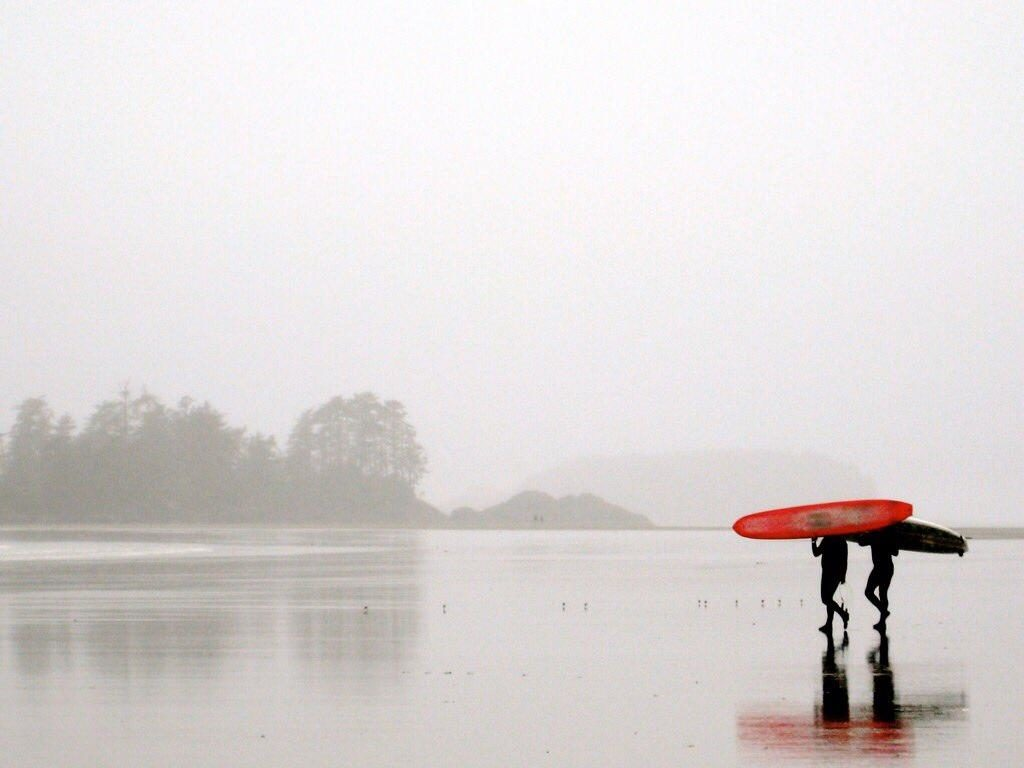Two people carry surfboards across a misty beach.