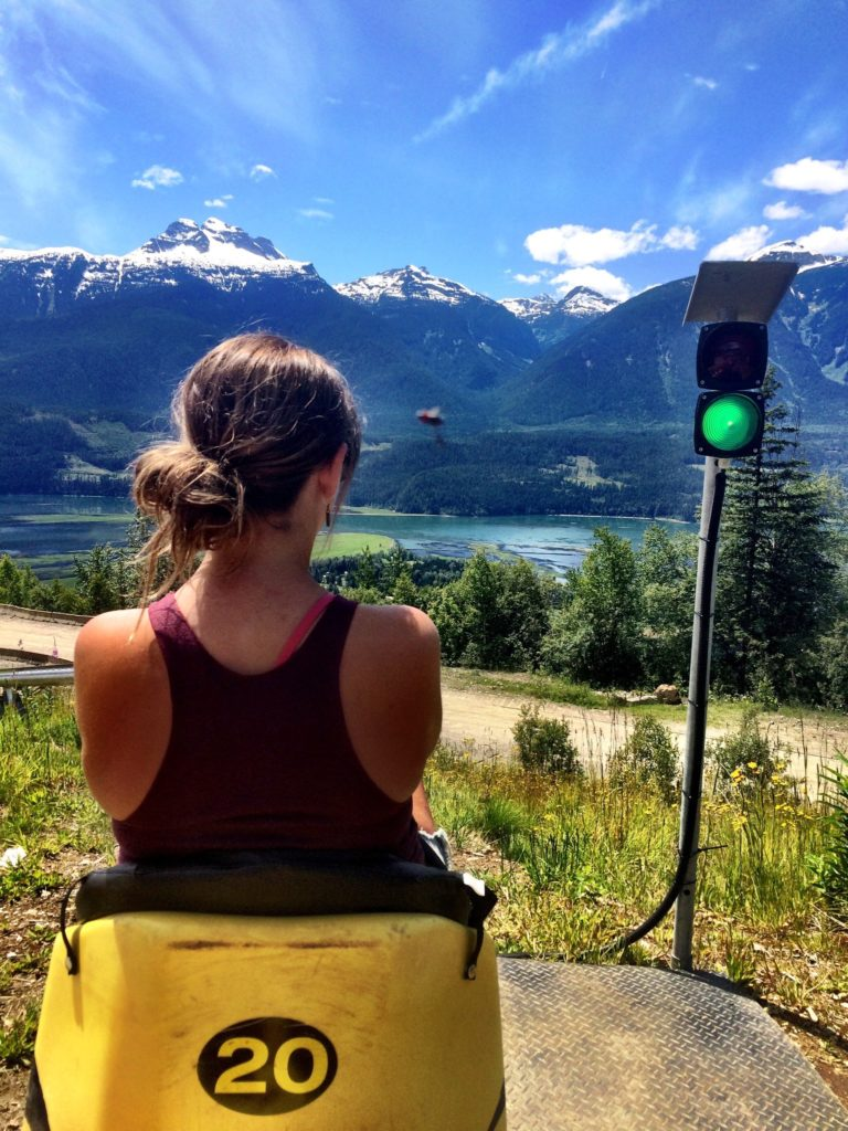 A woman sits in a yellow seat with the number 20 on the back at a green light. She is facing a view of snow-capped mountains.
