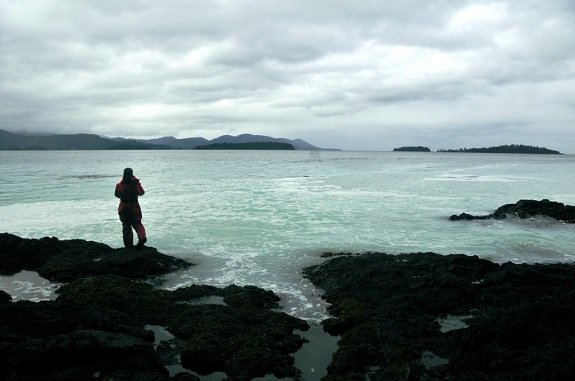 Silhouette of a woman standing at the edge of a turquoise ocean under a cloudy sky.