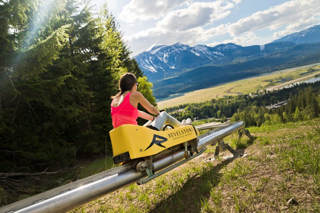 A woman rides a small rollercoaster that weaves through a mountainous landscape.