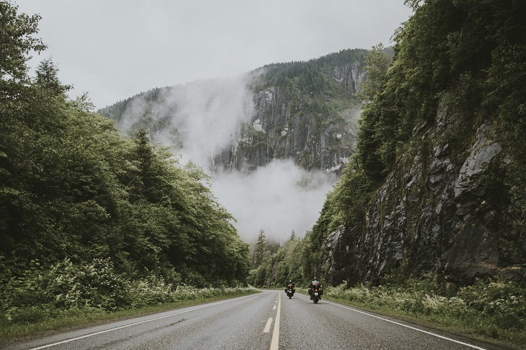 Two motorcycles travel on the highway towards a fog-covered mountain.