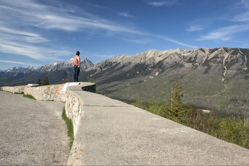 A man stands at the edge of a lookout, taking in a rocky mountain range.