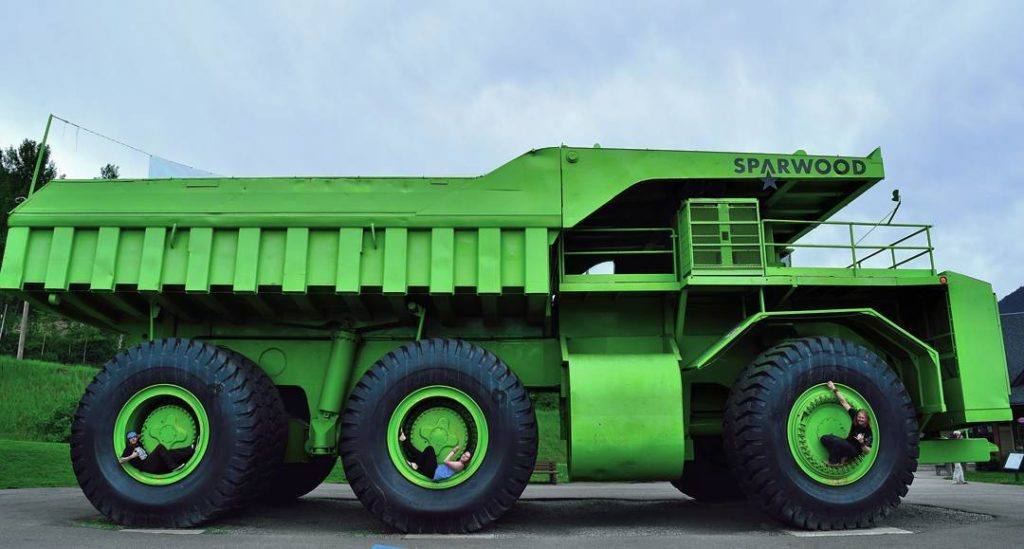 Three people sit in the wheel spokes of a giant green truck.