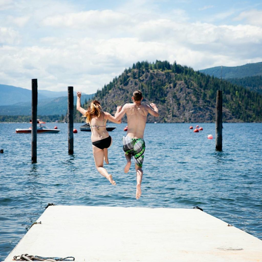 A man and a woman hold hands as they jump off a dock into the ocean.